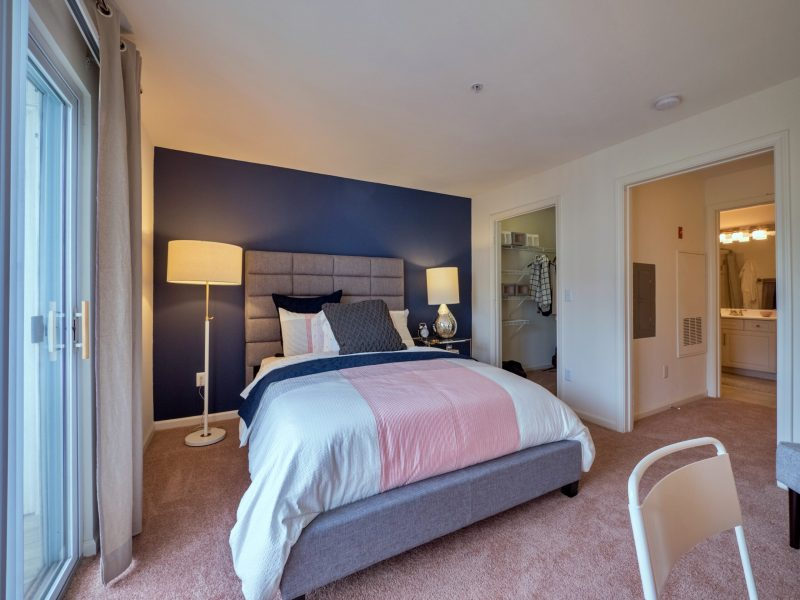 This image shows the bedroom area showcasing the light tone color wall, elegant fabrics, and an overlooking view outside that was ideal for a comfy pleasure.