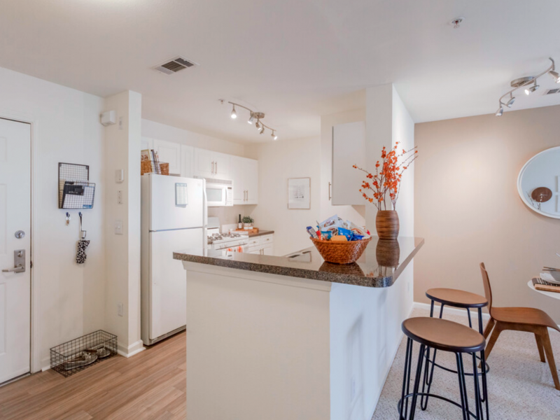 This image shows the kitchen island featuring the breakfast bar and granite-inspired countertops overviewing the dining area.